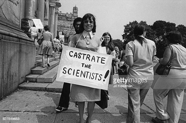 A protestor outside the American Museum of Natural History in Manhattan New York City holding a placard which reads 'Castrate the Scientists' 1976The...