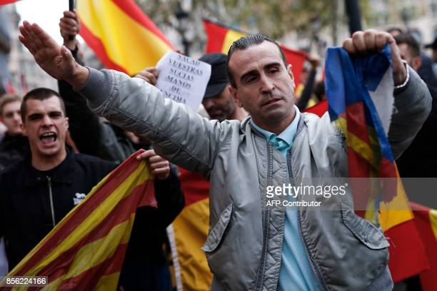 A protestor performs a fascist salute as he holds a torn 'Estelada' during a demonstration called by farright groups against a referendum on...