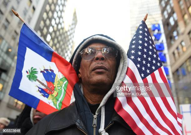 Protestor Pierre Gabriel from Haiti carries flags during a march on Martin Luther King Jr Day in Times Square called Rally Against Racism Stand Up...