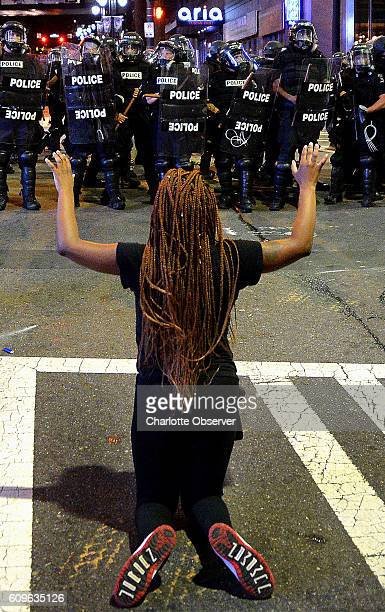 A protestor places her arms in the air while on her knees in front of Charlotte officers in riot gear at the intersection near the Epicentre in...