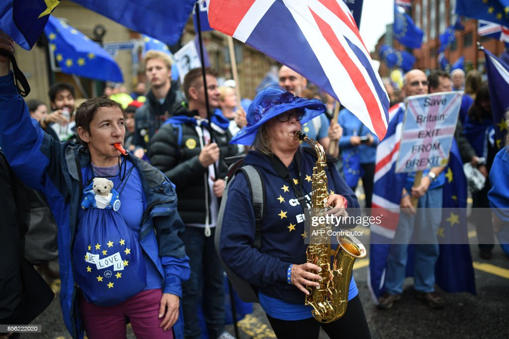A protestor plays 'Ode to Joy' on the saxophone during an anti-Brexit march on the first day of the Conservative Party annual conference in Manchester on October 1, 2017. British Prime Minister Theresa May's Conservative Party gathers on October 1, 2017, for its annual conference, dominated by questions about her leadership and splits on Brexit. / AFP PHOTO / Oli SCARFF
