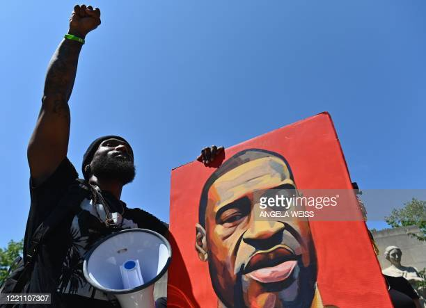 Protestor raises his fist while holding a painting of George Floyd during a Juneteenth rally at Cadman Plaza on June 19, 2020 in the Brooklyn Borough...