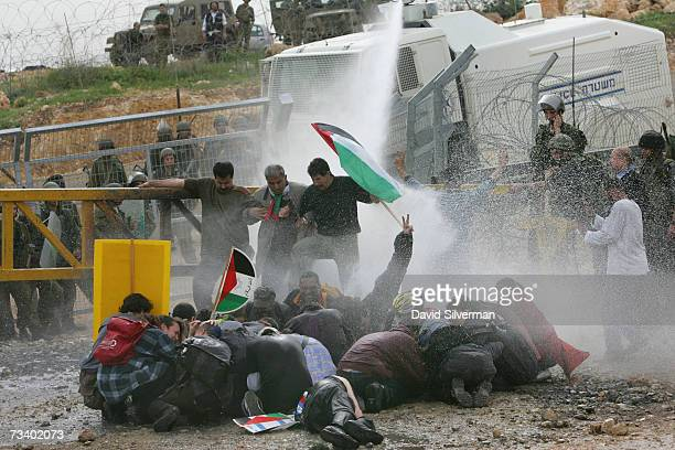 A protestor raising a victory salute is drenched by an Israeli police water cannon as it opens up against Palestinians leftwing Israelis and foreign...