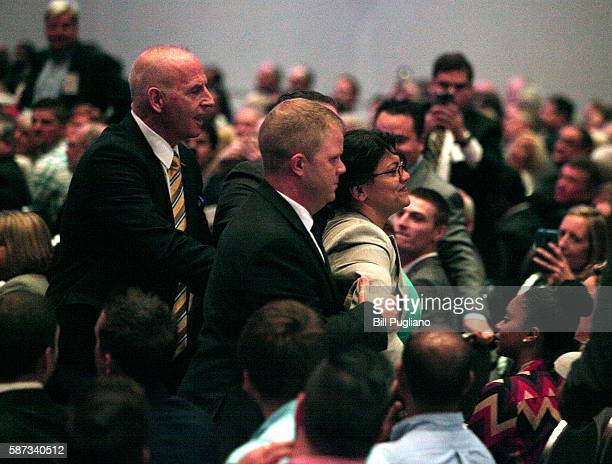 A protestor gets removed from the room after heckling Republican presidential candidate Donald Trump while he delivers an economic policy address...
