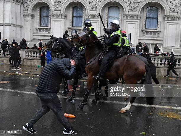 Protestor reacts as a mounted police officer raises their baton whilst riding along Whitehall, past the entrance to Downing Street, in central London...