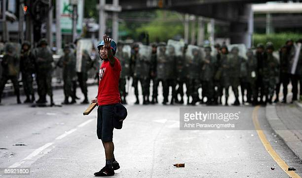 A protestor reacts in front of soldiers during a protest near Victory Monument on April 13 2009 in Bangkok Thailand Prime Minister Abhisit has called...