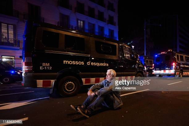 A protestor remains seated as Catalan Autonomous Police vans patrol the streets during a protest on October 26 2019 in Barcelona Spain Disturbances...