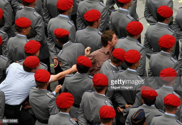 A protestor runs in between soldiers of the German Bundeswehr during a swearingin ceremony for new recruits at Marienplatz on July 30 2009 in Munich...
