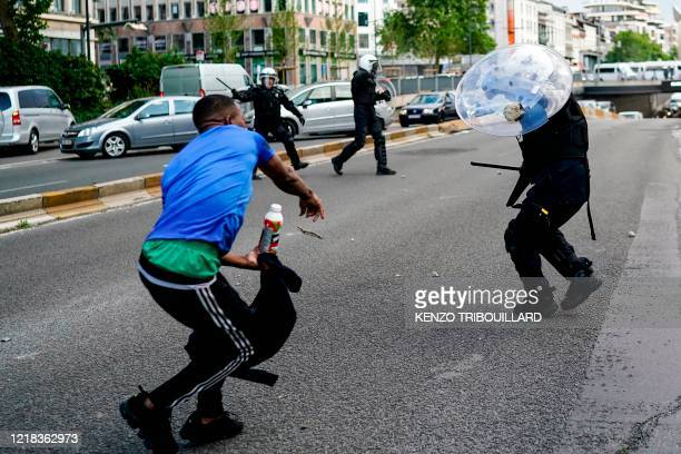 A protestor scuffle with Police officers in riot gear during an antiracism protest in Brussels on June 7 as part of a weekend of 'Black Lives Matter'...