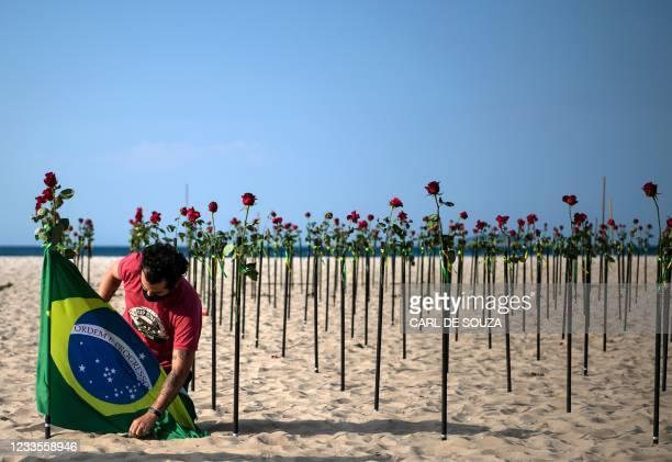 Protestor secures a Brazilian flag next to roses placed by the NGO Rio de Paz on Copacabana beach, Rio de Janeiro, in memory of Brazil's half a...