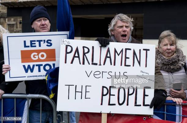 TOPSHOT A protestor shouts as he stands near the Houses of Parliament in London on March 13 2019 British MPs will vote Wednesday on whether the...