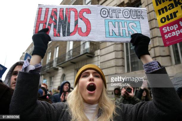 A protestor shouts slogans and carries a placard during a march calling for an end to the 'crisis' in the staterun National Health Service in central...