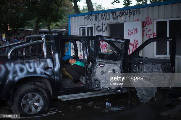 A protestor sleeps in a damaged car early morning at the Gezi park in Taksim Square on June 5 2013 in Istanbul Turkey The protests began initially...