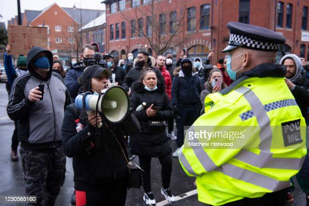 Protestor speaks into a megaphone near a police officer in front of Cardiff Bay police station on January 13, 2021 in Cardiff, Wales. Mohamud...