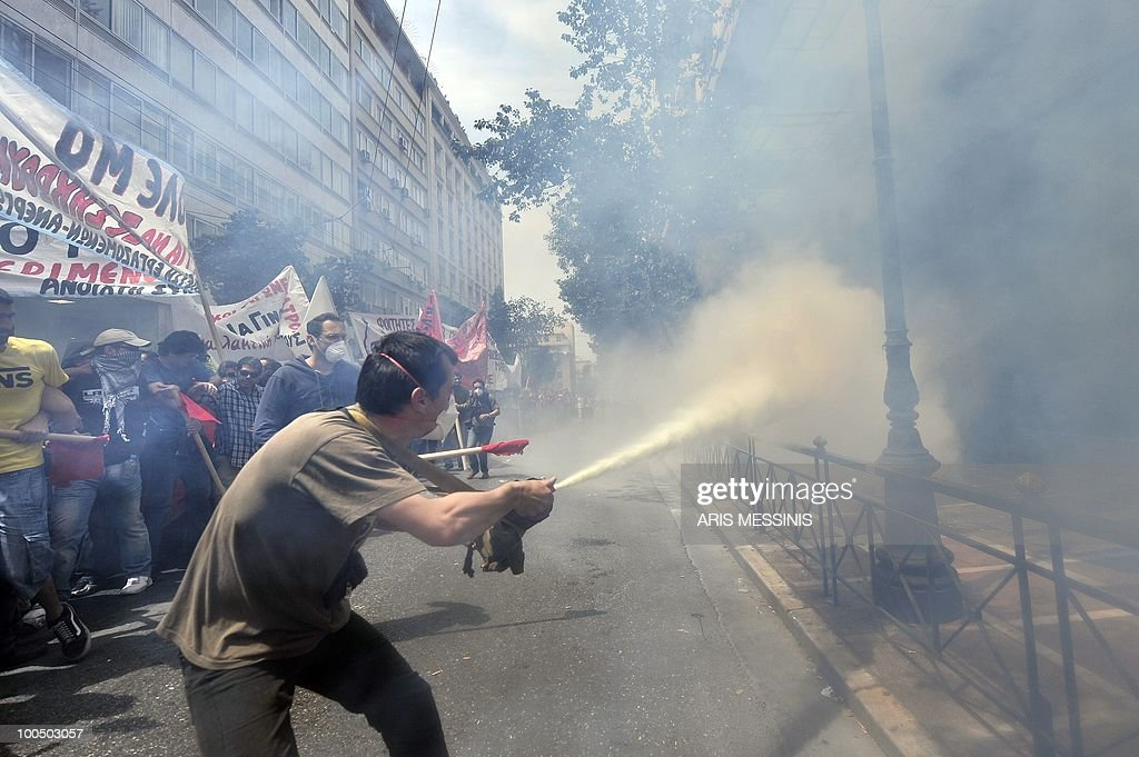 A protestor spray gas to greek riot policemen in the center of Athens on May 5, 2010. A nationwide general strike gripped Greece in the first major test of the socialist government's resolve to push through unprecedented austerity cuts needed to avert fiscal meltdown. Three people were killed in a firebomb attack on a bank in central Athens and around 20 people were being evacuated from the building, police said.