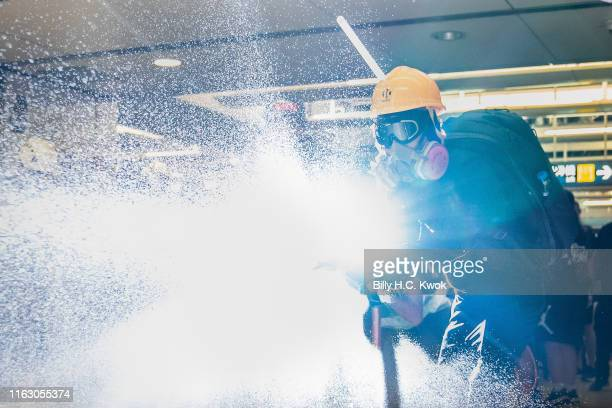 Protestor sprays a hose during a protest at the Yuen Long MTR station on August 21, 2019 in Hong Kong, China. Pro-democracy protesters have continued...