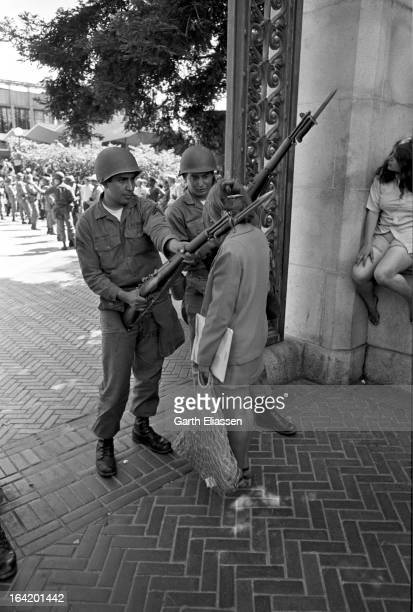 A protestor stands between two California National Guardsmen bayonets at the ready at the entrance to the University of Berkeley during protests...