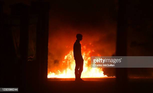 Protestor stands near a burning car as police attend the scene at Cloughfern as Loyalist protestors hijack and burn vehicles on April 3, 2021 in...