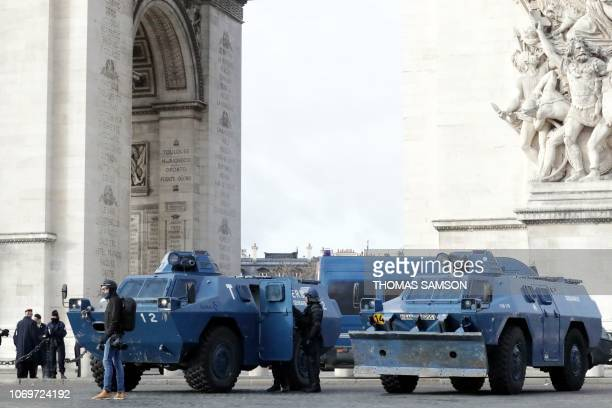 A protestor stands next to gendarmerie armored vehicles parked near the Arc de Triomphe in Paris on December 8 2018 during a yellow vests...