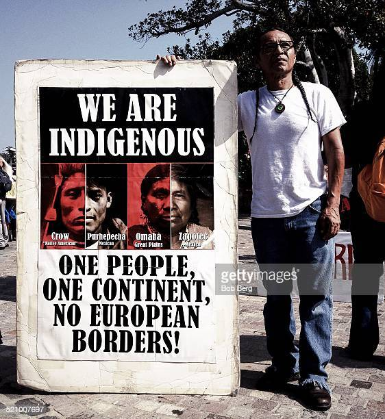 A protestor stands with a poster during the Protest and March Against Columbus Sunday Oct 12 2014 in Los Angeles