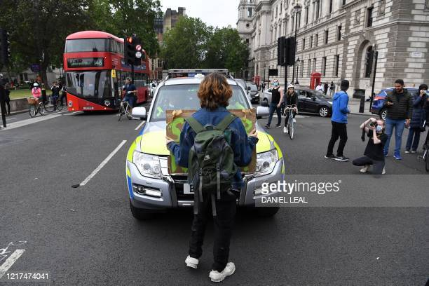 A protestor stops a police car in Parliament Square during an antiracism demonstration in London on June 3 after George Floyd an unarmed black man...
