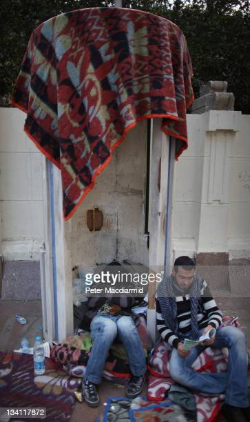 A protestor taking part in a sitin outside the government cabinet office sleeps inside a police sentry box while another reads on November 26 2011 in...