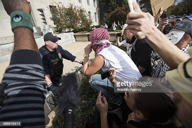 Protestor talks with a DHS Officer from a barrier in front of the Environmental Protection Agency during the Anonymous Million Mask March around the...