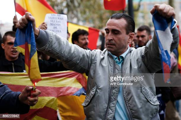 A protestor tears an 'Estelada' while another tries to burn it during a demonstration called by farright groups against a referendum on independence...