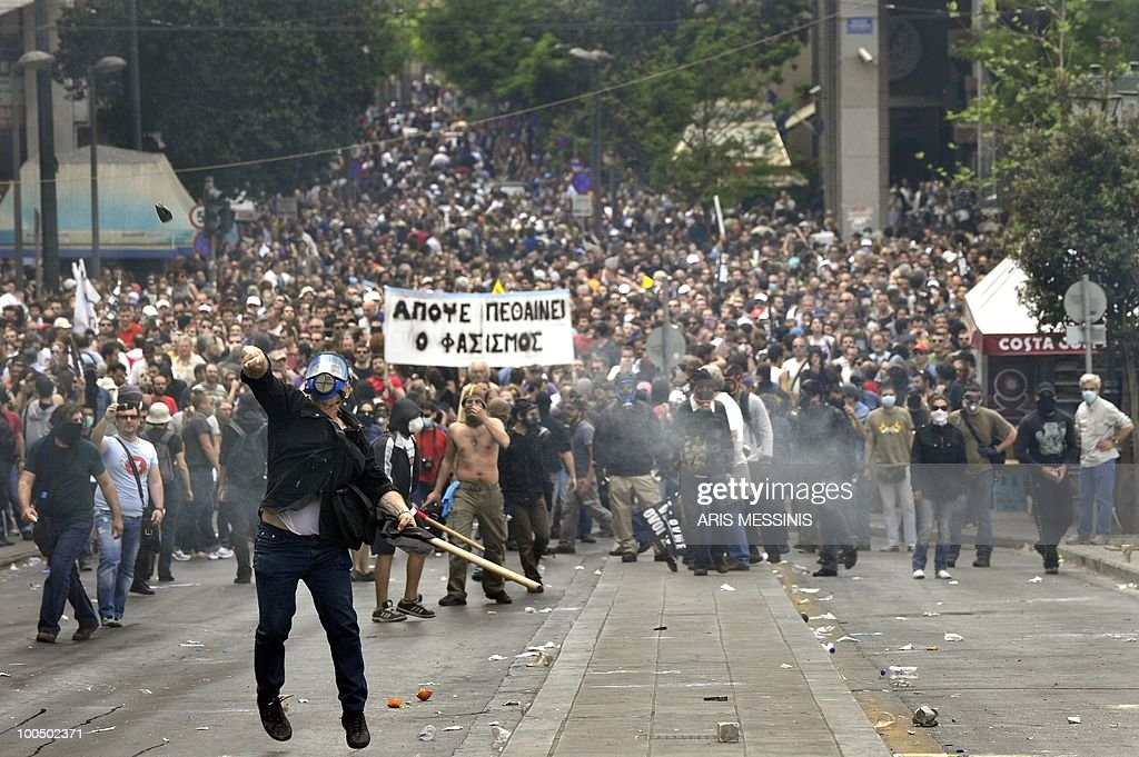 A protestor throwes a stone to police near the Parliament building in the center of Athens on May 5, 2010. A nationwide general strike gripped Greece in the first major test of the socialist government's resolve to push through unprecedented austerity cuts needed to avert fiscal meltdown.Three people were killed in a firebomb attack on a bank in central Athens and around 20 people were being evacuated from the building, police said.