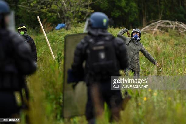 TOPSHOT A protestor throws a bottle towards riot gendarmes during clashes as part of a second eviction of environmental protesters from the area...
