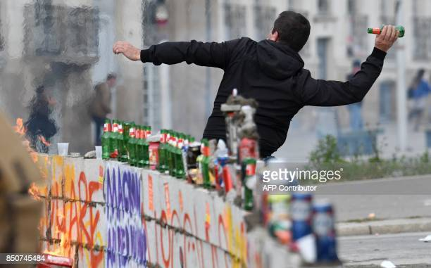 A protestor throws a glass bottle during a demonstration against French government proposed labour law reforms on September 21 2017 in Nantes / AFP...
