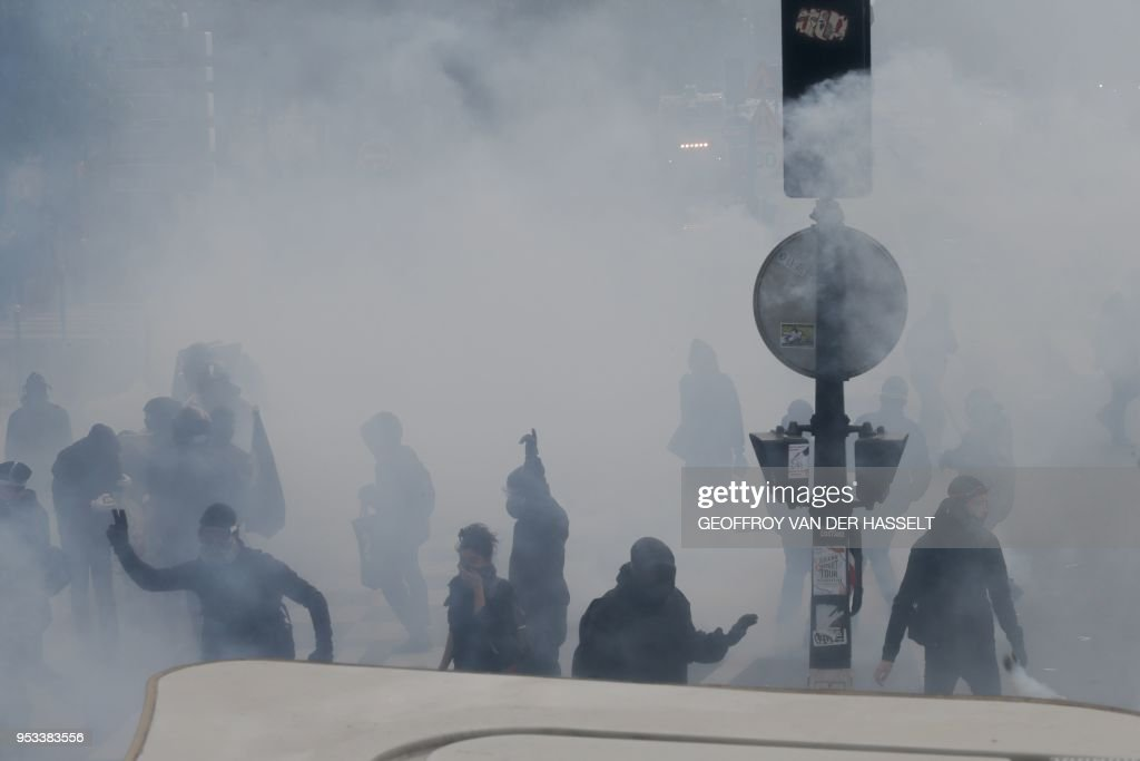 A protestor throws a missile towards unseen police officials as teargas clouds rise during a demonstration on the sidelines of a march for the annual May Day workers' rally in Paris on May 1, 2018.