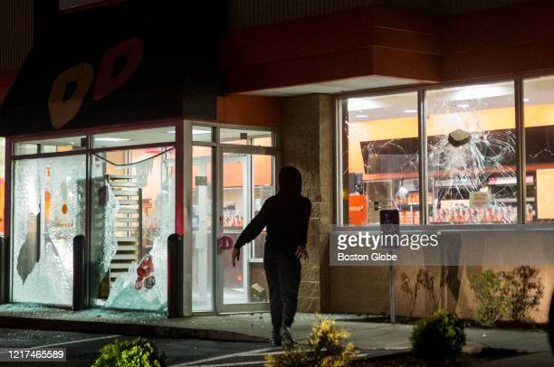 A protestor throws a paver stone through a Dunkin' window in Brockton MA as tensions escalate when a stand off with police pushes protestors back...