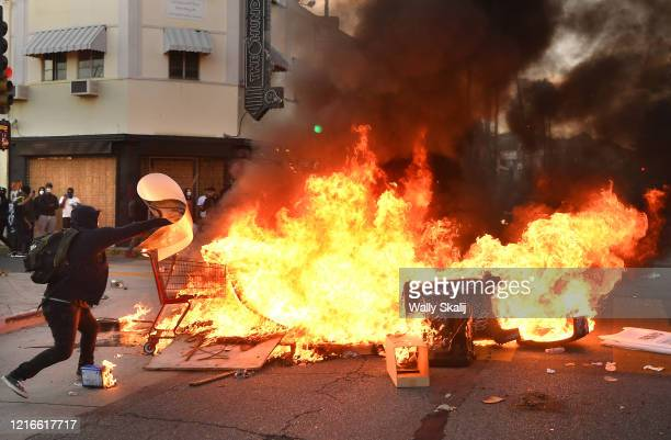Protestor throws a poster into a fire along Fairfax Ave. In Los Angeles Saturday.