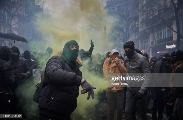 A protestor throws a rock towards police as protestors and French Riot Police clash during a rally near Place de Republique in support of the...