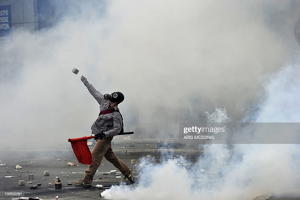 A protestor throws a stone to police near the Parliament building in the center of Athens on May 5, 2010. A nationwide general strike gripped Greece in the first major test of the socialist government's resolve to push through unprecedented austerity cuts needed to avert fiscal meltdown.Three people were killed in a firebomb attack on a bank in central Athens and around 20 people were being evacuated from the building, police said.