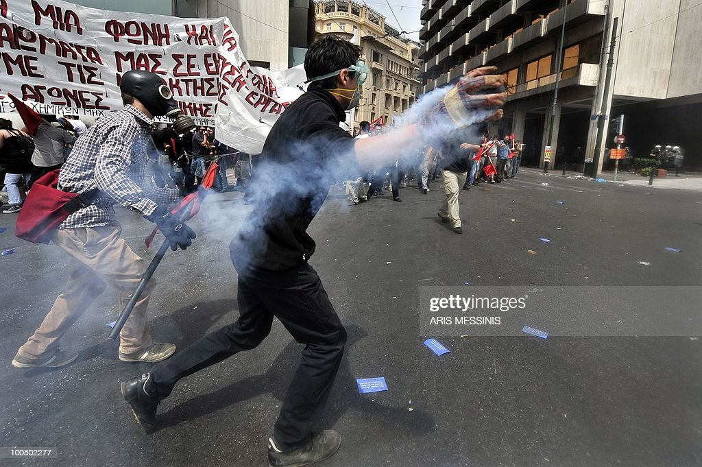 A protestor throws a tear gas canister shot from police lines during clashes in the center of Athens on May 5, 2010. A nationwide general strike gripped Greece in the first major test of the socialist government's resolve to push through unprecedented austerity cuts needed to avert fiscal meltdown. Three people were killed in a firebomb attack on a bank in central Athens and around 20 people were being evacuated from the building, police said.