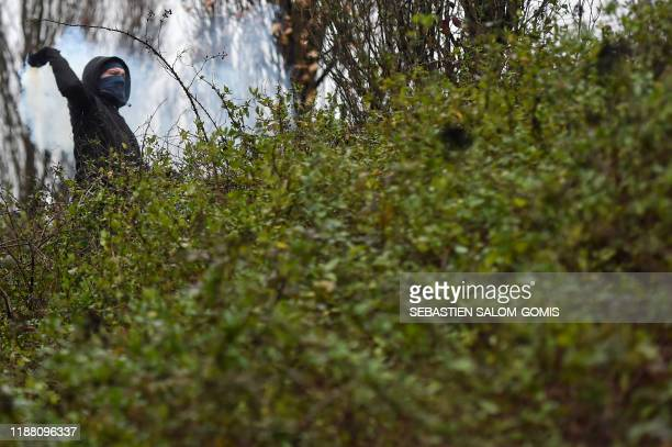 A protestor throws back a tear gas canister as they block Nantes' ring road in SaintHerblain near Nantes western France on December 12 2019 to...