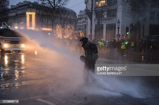 TOPSHOT A protestor tries to avoid water cannons used by French riot police during a yellow vests demonstration near the Champs Elysees Avenue in...