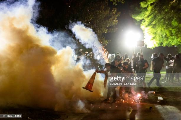 A protestor tries to put a traffic cone over a tear gas canister during a face off with police in front of the White House protesting the death of...