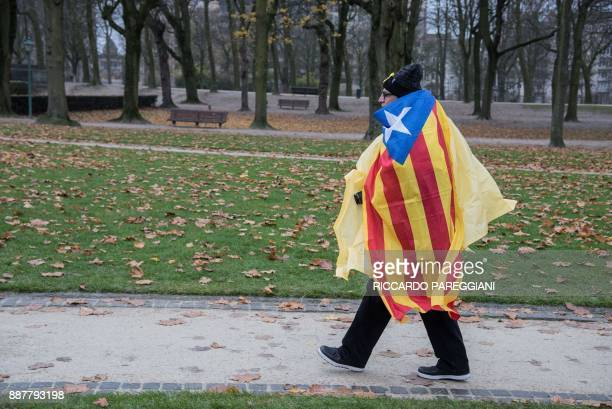 A protestor walks draped in a Catalan 'Estelada' flag as he attends a proindependence demonstration in Brussels on December 7 2017 A sea of around...