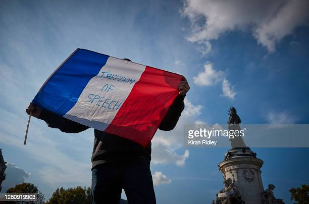 Protestor waves a French Tricolor flag with 'Freedom of Speech' written on it during an anti-terrorism vigil at Place de La Republique for the...