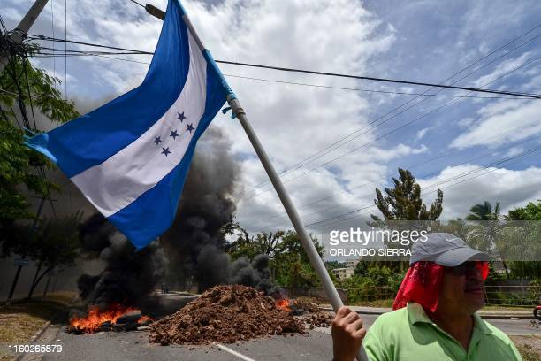 TOPSHOT A protestor waves a Honduran national flag during a protest demanding the resignation of Honduran President Juan Orlando Hernandez for his...