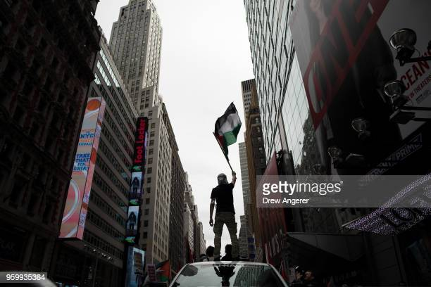 A protestor waves a Palestinian flag while standing atop a truck during rally in support of the Palestinian people in the wake of the recent violence...