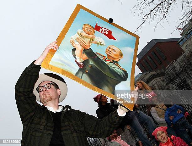 A protestor waves a poster of Russian President Vladimir Putin making reference to US President Donald Trumps' alleged close ties to Russia during...