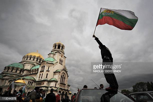 Protestor waves Bulgarian flag on top of a car during a protest in front of the goldendomed Alexander Nevski cathedral in Sofia on April 28 2011...
