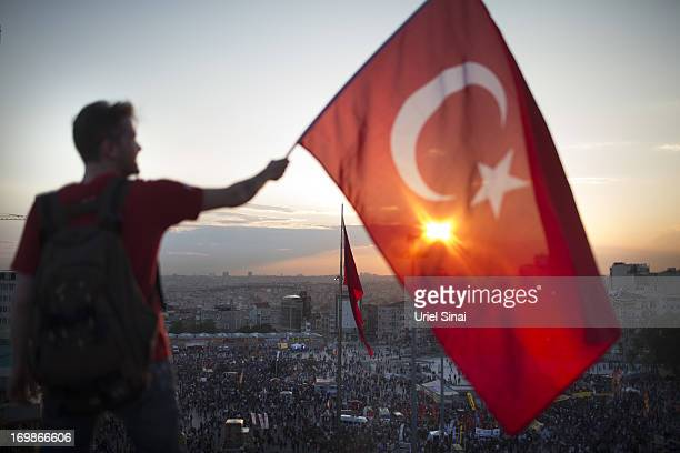 A protestor waves the Turkish flag from a roof top at Taksim square on June 3 2013 in Istanbul Turkey The protests began initially over the fate of...