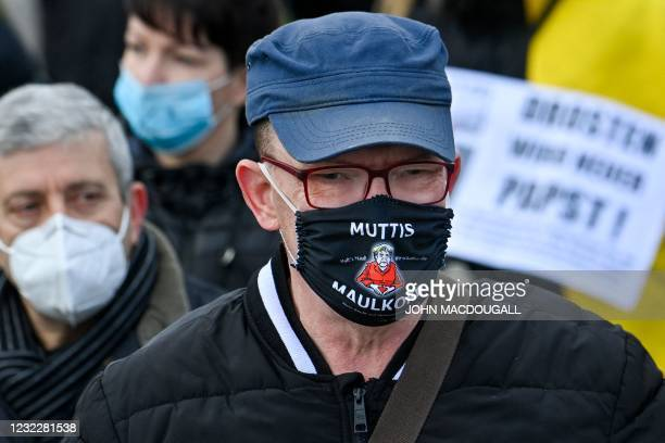 """Protestor wearing a face mask with a cartoon of German Chancellor Angela Merkel, reading """"Mummys muzzle"""" takes part in a demonstration in Berlin on..."""