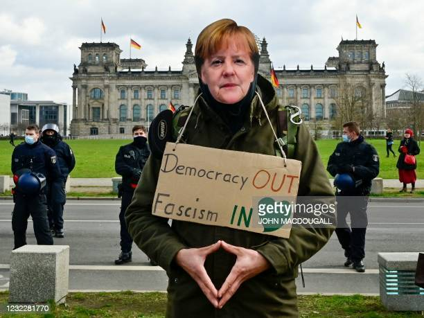 Protestor wearing a mask depicting German Chancellor Angela Merkel takes part in a demonstration in Berlin on April 2021, as anti lockdown critics...