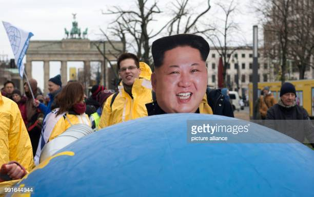 A protestor wearing a mask of North Korean leader Kim Jong Un takes part in a demonstration against nuclear weapons politics under the slogan 'Stop...
